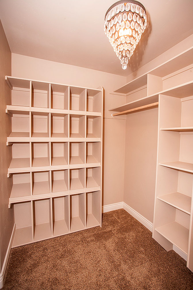 Master bedroom walk-in-closet with built in shelving and ample storage.