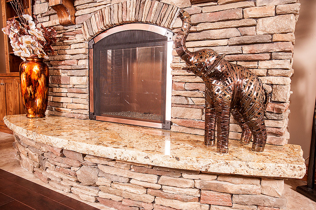 Copper banding around fireplace, rock hearth and granite plate