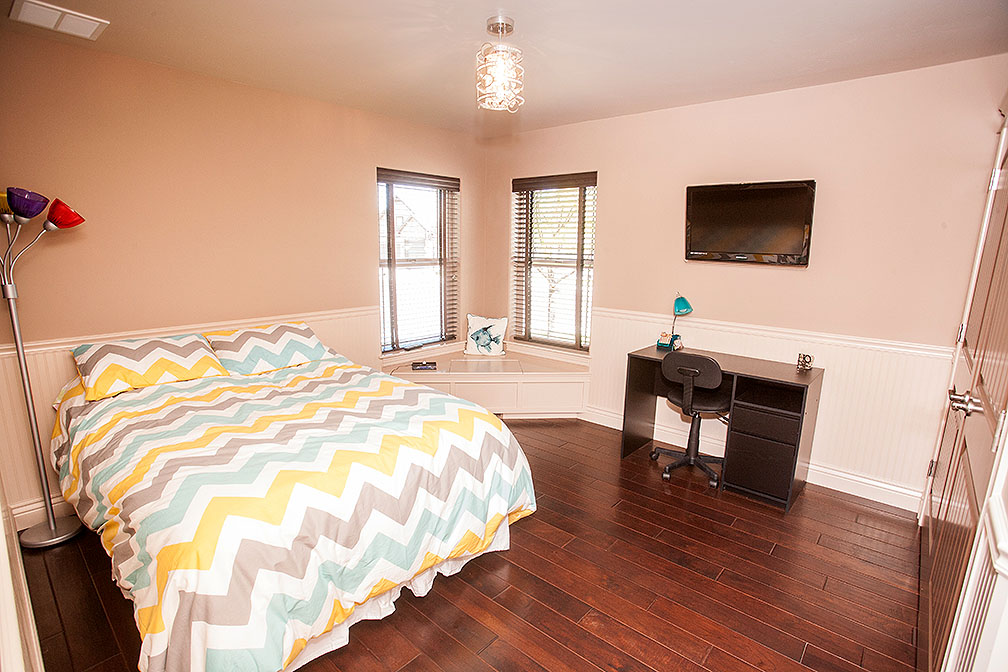 Bedrrom with wood floors and wainscoting
