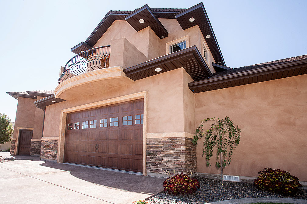 Stucco, brick, wood garage doors, balcony