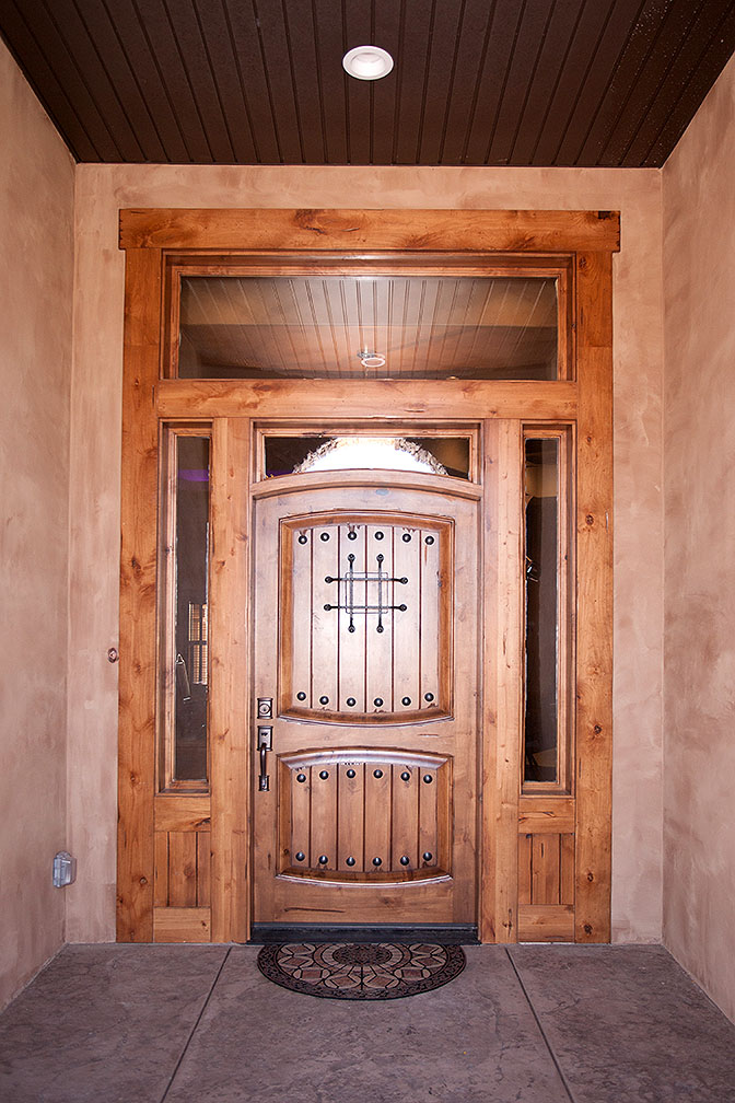 Front entry solid wood door with brass hardware.