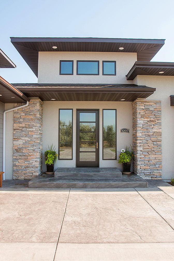 Outside the entry way is stamped and colored concrete with beautiful rock lined corners.