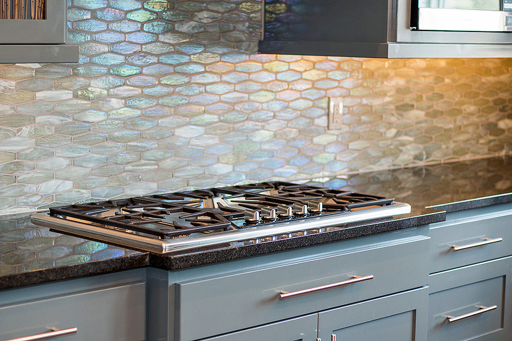 Gray shaker cabinets adorned with brushed nickel hardware, stainless cooktop, and gorgeous backsplash.