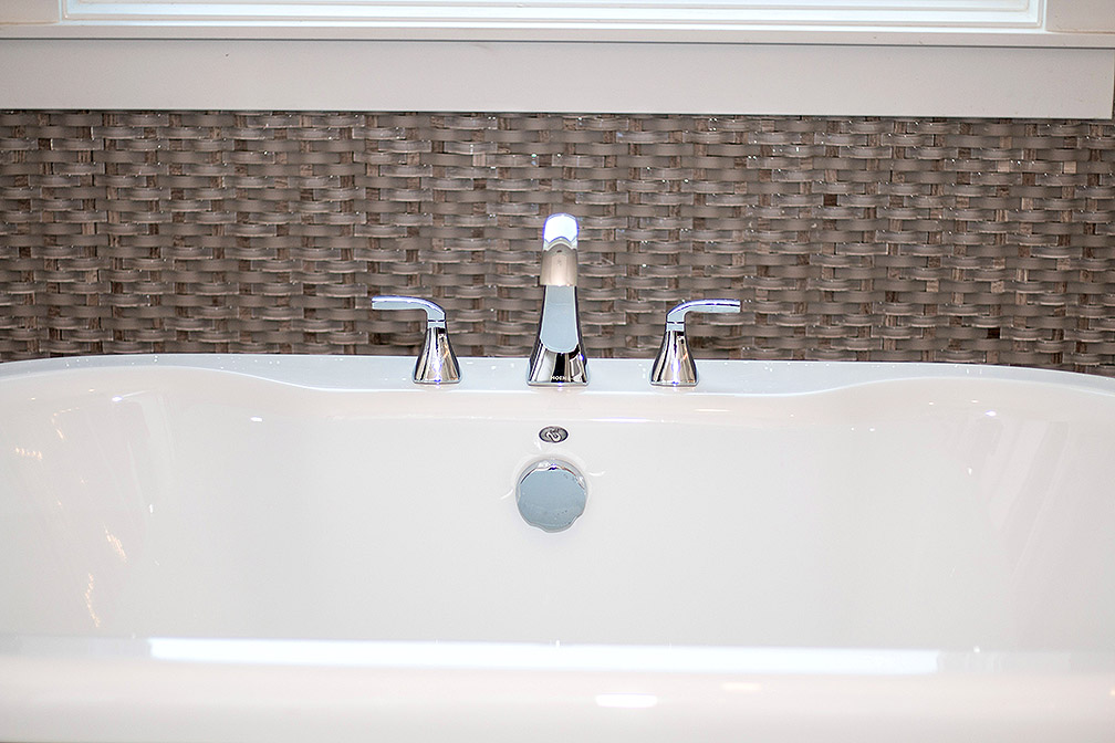 Basket weave tile creates a nice backdrop to this stand alone tub in the master bathroom.