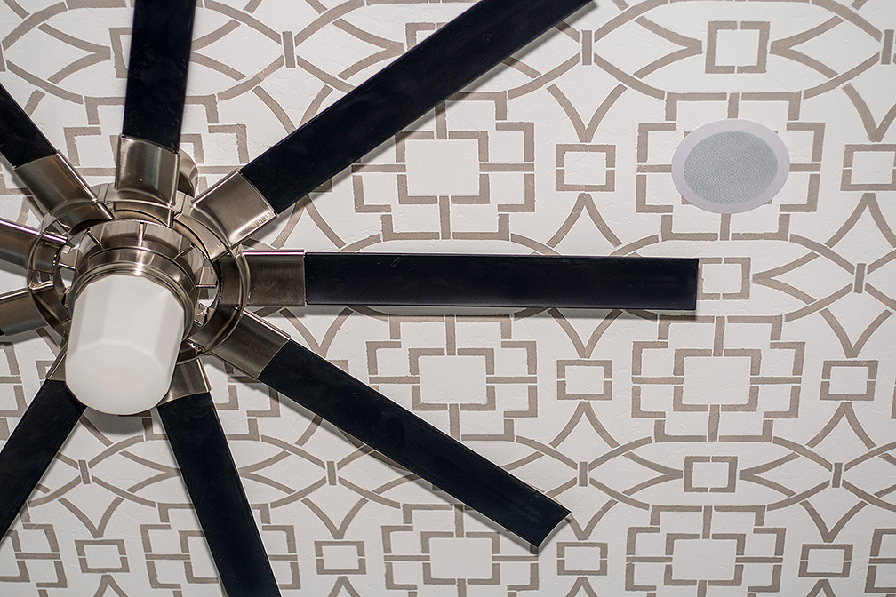 Painted tray ceiling with modern ceiling fan in master bedroom.