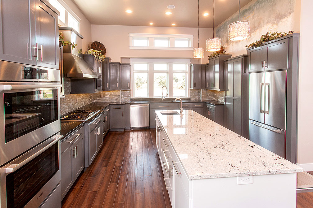 Double ovens, gas stovetop range, massive kitchen island and oversized hidden pantry.