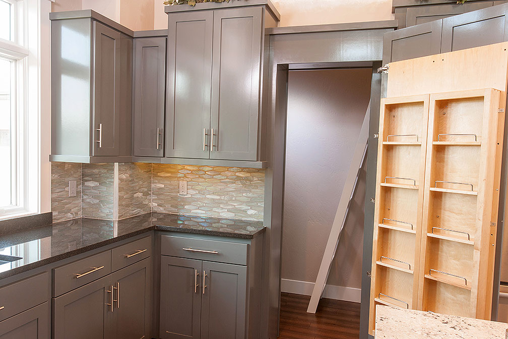 Hidden pantry offers ample storage and has a ladder leading up to a large storage cubby.