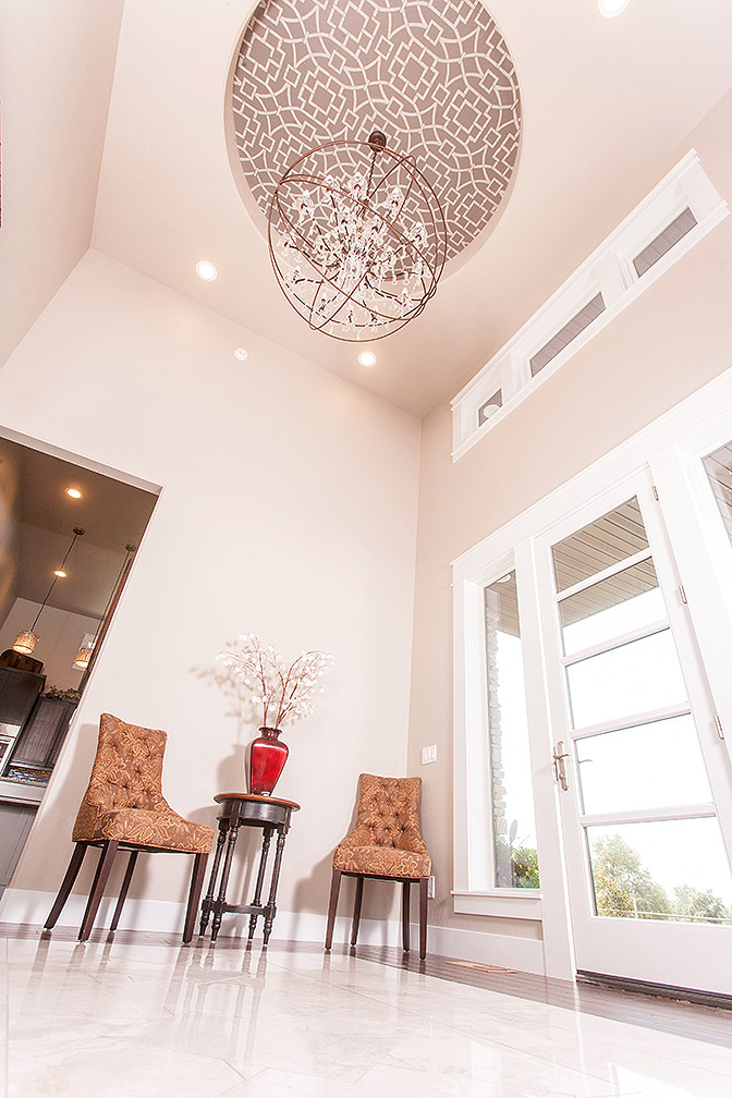 This entry way has 18 foot walls leading your eye up to painted tray ceiling and jaw-dropping chandelier.