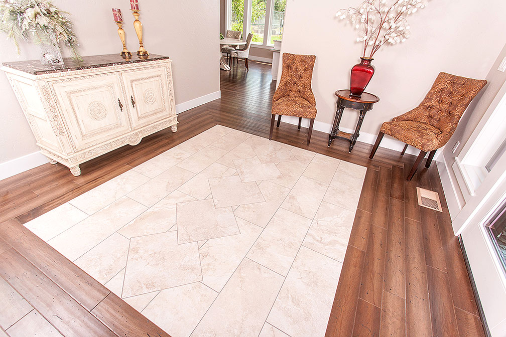 Entry way with a polished Travertine tile design and bordered with engineered wood flooring.