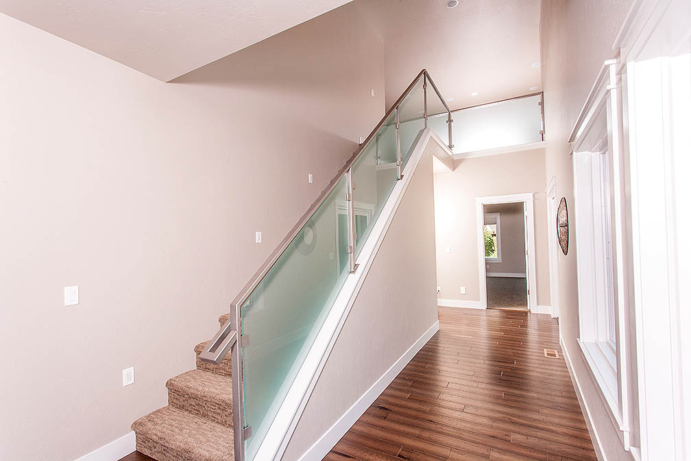 Modern staircase leading up to large bonus room and wide hallways with beautiful views of the courtyard.