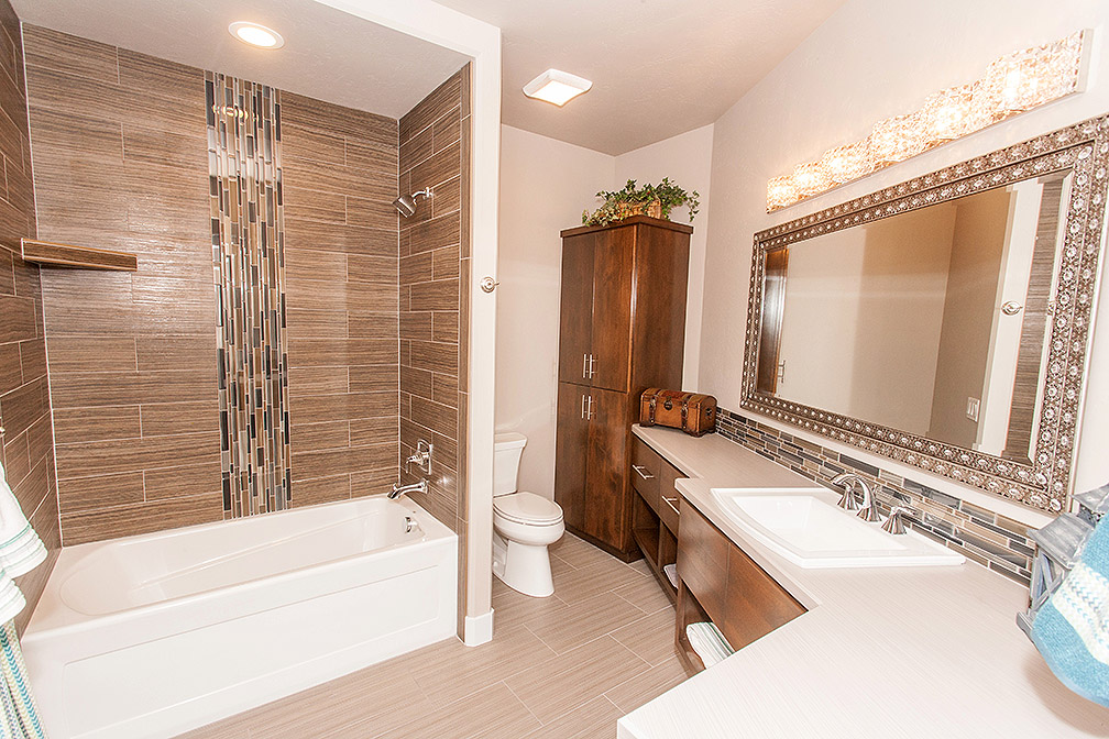 This bathroom on the main level has ample storage and is adorned with stunning lighting and large bathroom mirror.