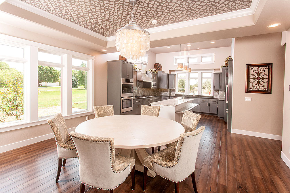 No details spared in this house. Our clients carefully chose very unique yet stunning light fixturThe painted tray ceiling above the dining table helped to create its own space in the open floor plan. es for their home.