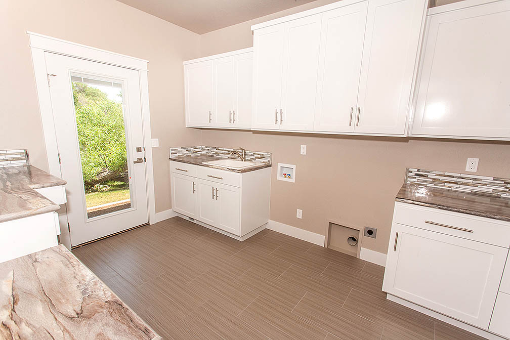 This large laundry room is has ample storage, bright light and sophisticated flooring.